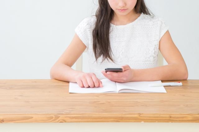 スマホを見ながら勉強する女の子