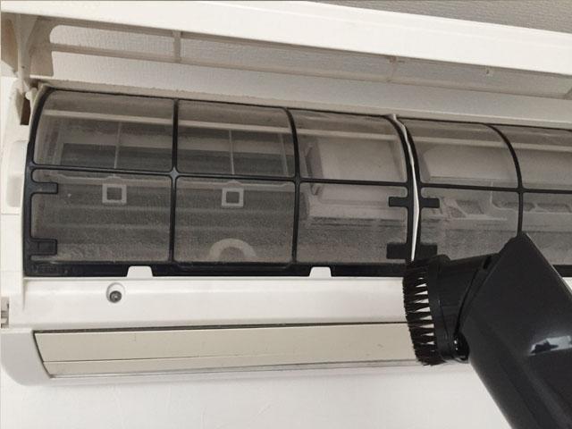 エアコンの埃を掃除機で吸い取る